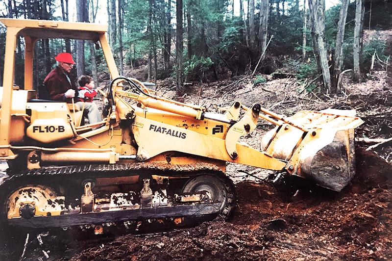 man and child operating a piece of heavy machinery together